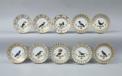 Suite of TEN PLATES after the South American Bird Service in porcelain with polychrome and gold decoration in the center of an exotic bird placed on a garland of gold foliage tied on two supports in the Greek style, the wing decorated with a frieze of...