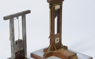 "Two masterpieces depicting two ""Guillotines"", one in wood, copper, brass and ivory resting on a rectangular base and the second in chrome-plated metal. Period: late 19th and early 20th century. H.(out of the base):21,3 and 23,8cm."