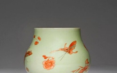 A CHINESE IRON-RED ENAMELLED CELADON-GROUND 'BUTTERFLY' VASE 19TH CENTURY The squat pear-shaped body painted with three butterflies in flight amidst sprays of flowers, with areas of detail picked out in grey and gilt, all reserved on a pale green...