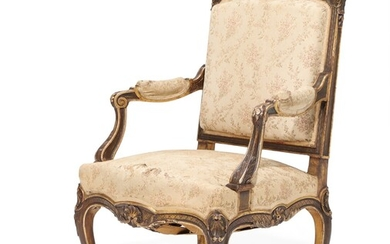 A French 19th century gilt and dark patinated wood Napoleon III armchair, carved with flowers and foliage.