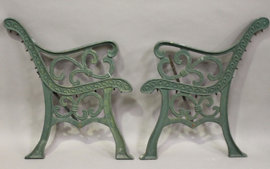 A pair of early 20th century green painted cast iron garden bench ends of scrolling form, height 78c