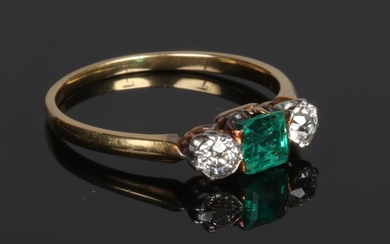 A yellow metal emerald and diamond three stone ring. With sq...