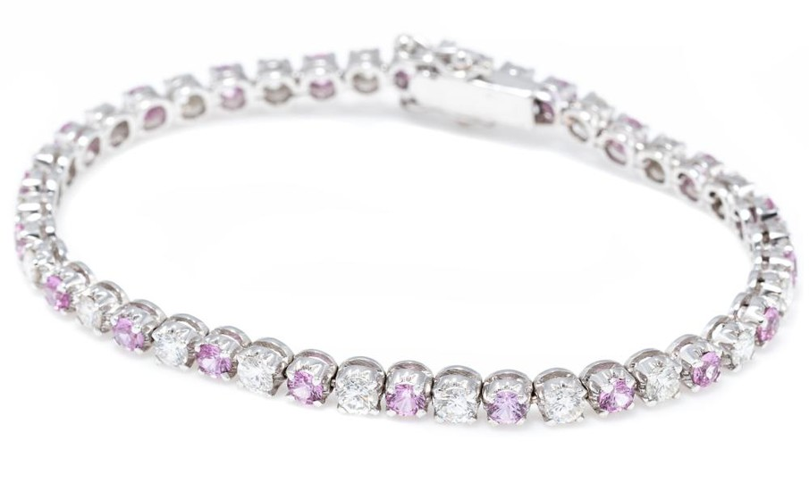 AN 18CT WHITE GOLD PINK SAPPHIRE AND DIAMOND LINE BRACELET; alternately set with a round brilliant cut diamond and a pink sapphire t...