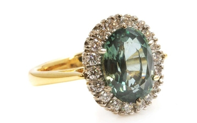 An 18ct yellow and white gold green sapphire and diamond oval cluster ring