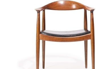 """Hans J. Wegner: """"The chair"""". Nutwood armchair, upholstered in seat with black leather. Made by cabinetmaker Johannes Hansen."""