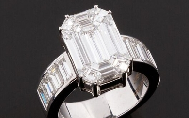 Ring in 18k white gold (750 thousandths) producing an astonishing diamond trompe-l'oeil thanks to the perfect juxtaposition of nine fancy cut diamonds giving the impression of a very large emerald cut diamond. This ring is the result of the perfect...