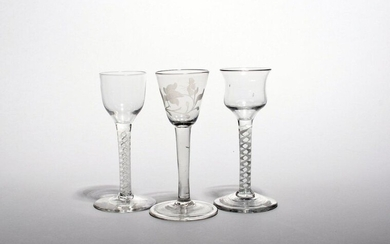 Three small wine glasses c.1760, one with a rounded funnel bowl engraved with a flower raised on a plain stem above a folded foot, the others with ogee and waisted bowls raised on opaque twist stems, 14.4cm max. (3)