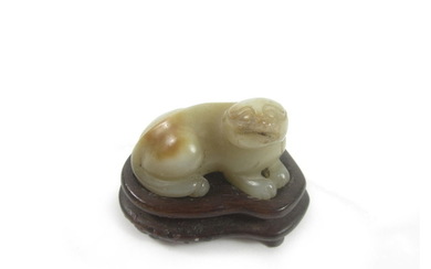 A carved jade lion-dog and wood stand