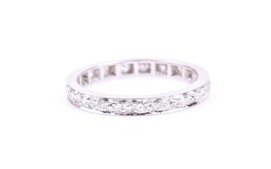 A diamond eternity band ring, the white metal shank inset wi...