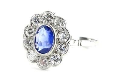 A sapphire and diamond cluster ring, with central oval...