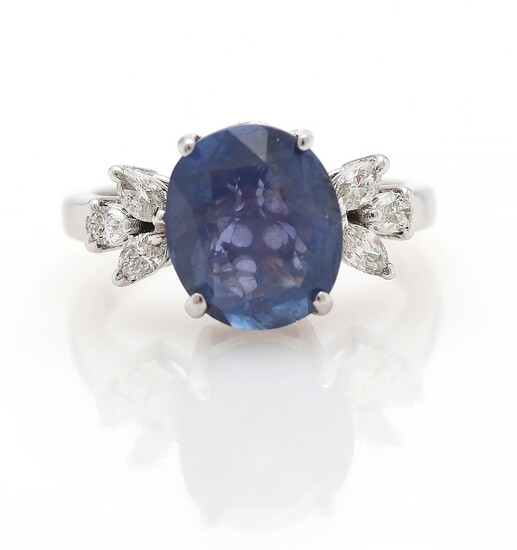 NOT SOLD. A sapphire and diamond ring set with an oval-cut sapphire flanked by six...