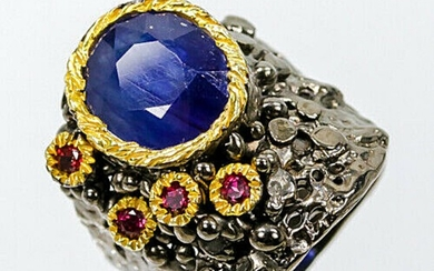 A sapphire and garnet ring set with a circular-cut sapphire and numerous pink rhodolite garnets, mounted in black rhodium and gold plated sterling silver.