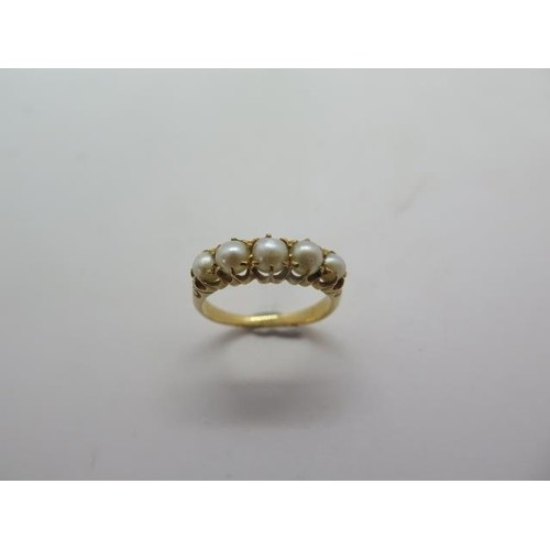 A yellow gold ring set with five pearls, no hallmark but tes...