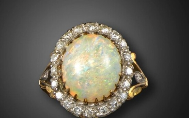 An opal and diamond cluster ring, the solid white opal cabochon is set within a surround of single-cut diamonds in platinum and gold, size M 1/2