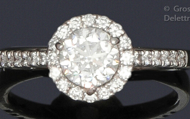"""Ring """" Solitaire """" in white gold, adorned with a brilliant-cut diamond surrounded and shouldered by smaller diamonds. Tour of doigt : 53. P. Brut : 3.2 g. Weight of diamant : 1 carat. Couleur : E. Pureté : VS1. The diamond is accompanied by a..."""