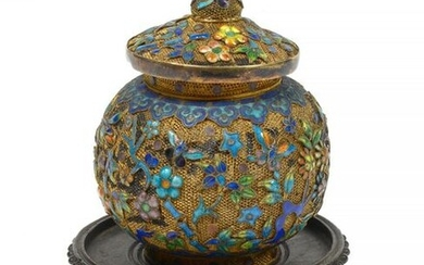 Small round box covered in gilded fishnet decorated with enamelled silver floral decoration.Chinese work. Circa 1900. Resting on a carved wood base. (Light blows). H.:+/-8,2cm.