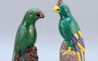 """TWO CHINESE POLYCHROME PORCELAIN PARROT FIGURES Standing on aubergine rockery bases. Heights 10"""" and 11""""."""