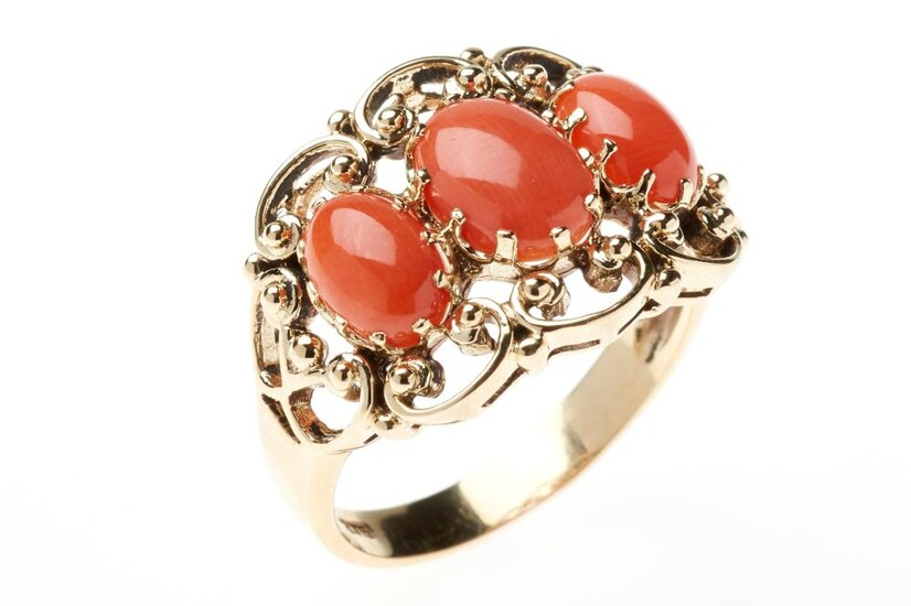 A NOUVEAU STYLE CORAL RING; set in a 9ct gold scrolling mount with 3 oval cabochon corals, size N, top 14 x 18mm, wt. 4.3g.