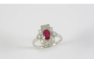 A RUBY AND DIAMOND CLUSTER RING the oval-shaped ruby is set ...