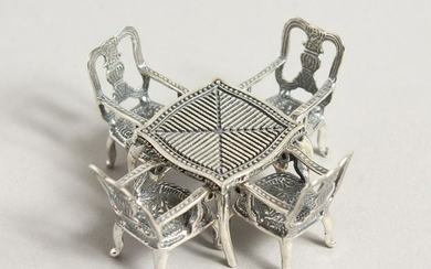 A SILVER MINIATURE TABLE AND FOUR CHAIRS.