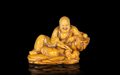 A gilt-decorated soapstone carving of the Laughing Lion Luohan