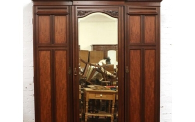 A late Victorian mahogany triple mirror front wardrobe. With...