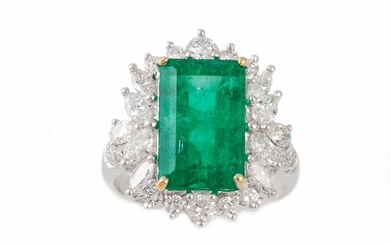 AN EMERALD AND DIAMOND CLUSTER RING, the trap cut emerald to...