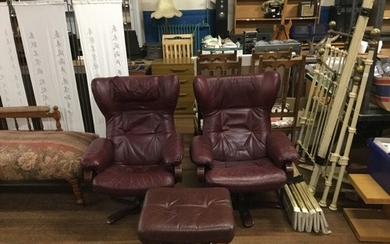 Pair of oxblood leather lounge chairs with matching stool.