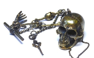 A BRASS SKULL FORM SNUFF BOX AND MATCHING ALBERT CHAIN The c...