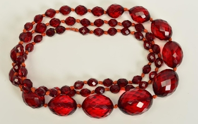 A FACETED RED PLASTIC BEAD NECKLACE, designed as a single ro...