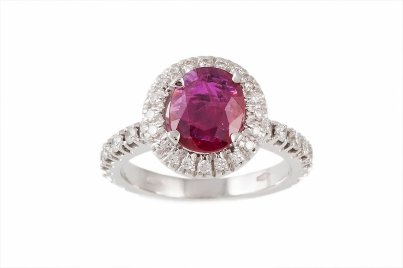 A RUBY AND DIAMOND CLUSTER RING, the cushion cut ruby to a b...