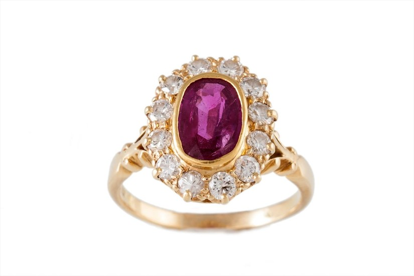 A RUBY AND DIAMOND CLUSTER RING, the oval ruby to a surround...