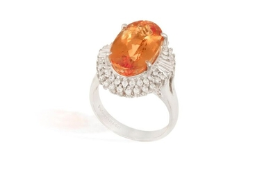 A TOPAZ AND DIAMOND CLUSTER RING The elongated oval-shaped topaz...