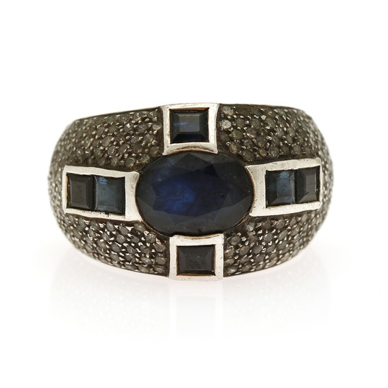 A sapphire and diamond ring set with an oval- and six square-cut sapphires encircled by numerous single-cut diamonds, mounted in silver. Size 58.