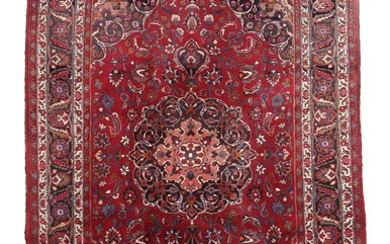 A signed Persian carpet, classical medallion design with entwined branches, ornaments, flowers and foliage on red base. 20th century. 312×205 cm.