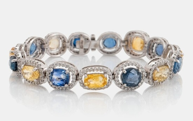 An 18K white gold bracelet set with faceted blue and yellow sapphires with a total weight of 25.80 cts