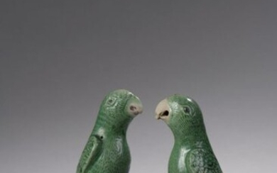Pair of yellow and green enamelled porcelain subjects on the biscuit, depicting parakeets on a rock. On their openwork wooden bases.