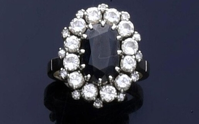 Ring in 750e white gold set with an oval sapphire of about 2 ct, in a double diamond surround.
