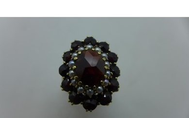 A 9ct gold Bohemian garnet and seed pearl oval cluster ring,...