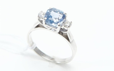A CEYLONESE SAPPHIRE AND DIAMOND RING IN RHODIUM PLATED 18CT GOLD, THE SQUARE EMERALD CUT BLUE SAPPHIRE WEIGHING 2.75CTS, FLANKED BY...