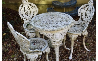 A Victorian style painted cast metal garden table, three mat...