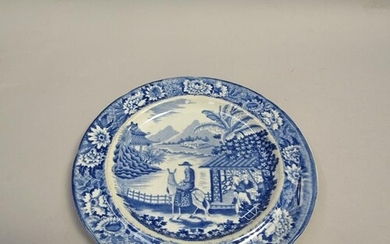 A blue and white plate printed with a man riding a mule besi...