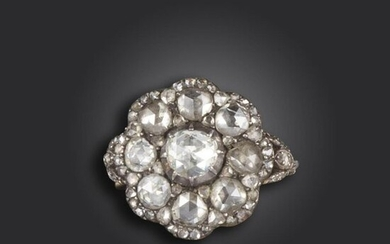 A diamond cluster ring, of flowerhead design and set with rose-cut diamonds in silver on gold closed-back setting, with further diamonds to the foliate shoulders, size M approximately