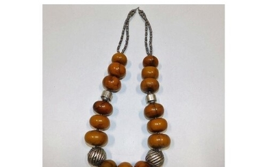 A large ethnic amber necklace with white metal fittings, tes...