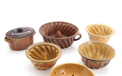 Four pudding moulds, strainer and paté mould of glazed earthenware. 19th century. Pudding moulds Diam. 21–29 cm. (6)