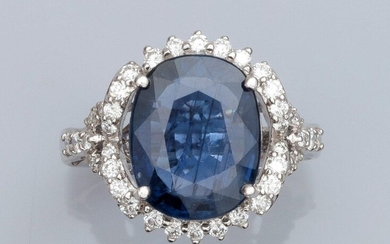 """Ring in 750°/00 (18K) white gold, set with an 8.05 carats cushion natural sapphire, surrounded by brilliant-cut diamonds. Laboratory certificate """"No heat treatment observed"""". 7.4 g. TDD 53. Width: 17.4 mm. Eagle head punch"""