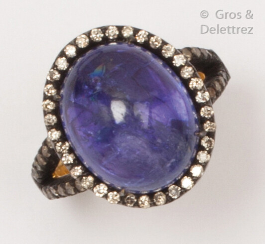 Yellow gold and blackened silver ring, adorned with a tanzanite cabochon in a setting of brilliant-cut diamonds. Finger size: 53. P. Rough: 7.4g.