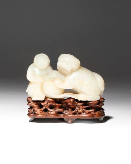A CHINESE PALE CELADON JADE CARVING OF A BOY AND...