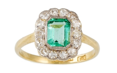A DIAMOND AND EMERALD CLUSTER RING, the trap cut emerald to ...