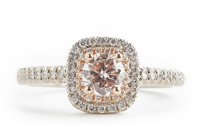 A diamond ring with a natural fancy light orangy pink diamond weighing app. 0.44 ct. and diamonds weighing app. 0.30 ct., mounted in 18k white and pink gold.